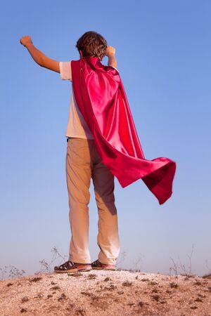 空の背景、丘の上に赤いマントで十代のスーパー ヒーローのスーパー ヒーローを弾いている少年