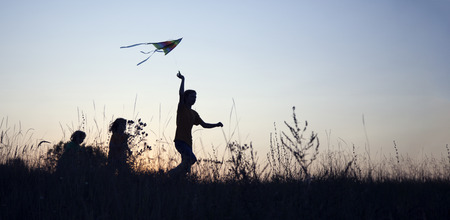 Children playing kite on summer sunset meadow silhouetted. Stock Photo