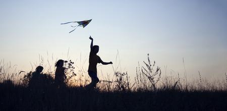 Children playing kite on summer sunset meadow silhouetted. Standard-Bild