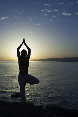 Beauty girl on beach in yoga pose, relax silhouette. Stock Photo