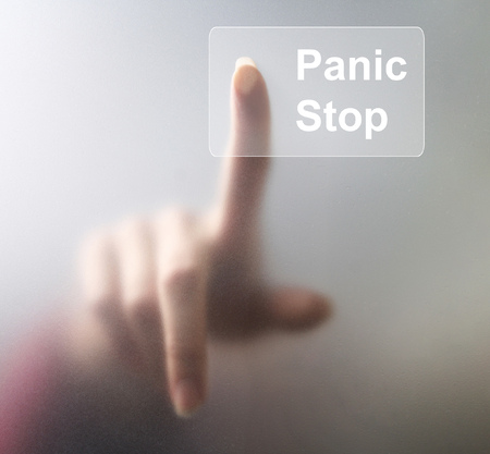 Panic Stop button. A finger pressing a glass panic button on grey