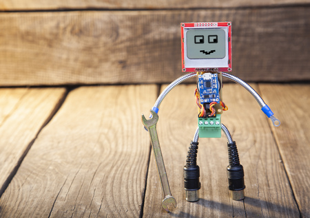 Robot made of parts of circuit boards with wrench, on wood Stock Photo