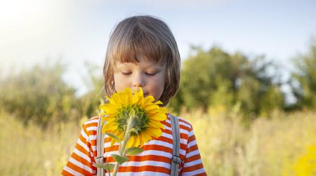Happy boy with sunflower outdoors. Children play in garden.