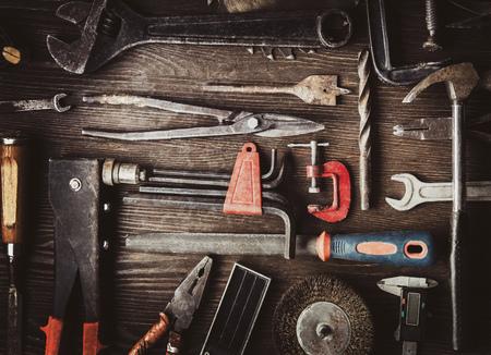 schmuddelige alte Werkzeuge auf einem hölzernen Hintergrund (Verarbeitung prozessübergreifend)
