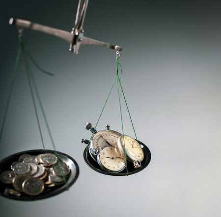 old scales with money and hours on plates, concept time is money Stok Fotoğraf