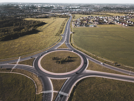 Top down aerial view of a traffic roundabout on a main road.