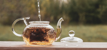 Filling the kettle with boiling water tea drinking on the veranda nature Imagens