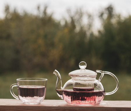 Teapot with fragrant herbal tea on a background of nature. Imagens