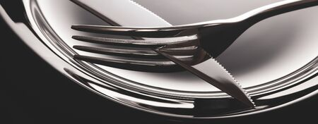 Empty plate with spoon, knife and fork on a black background.