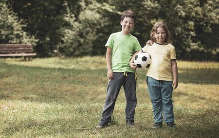 Two child soccer player. Boy with ball on green grass. Stockfoto