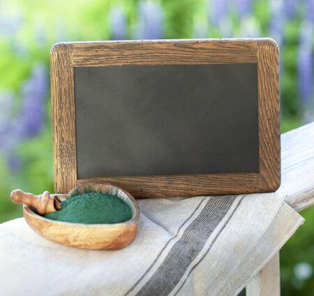 Organic spirulina algae powder in a wooden spoon on green grass background. black board Standard-Bild - 128549977