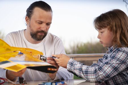 son and father made homemade radio-controlled model aircraft (airplane is hand made not copyright)