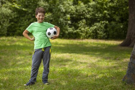 child play soccer player. Boy with ball on green grass.