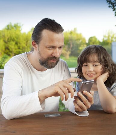 father and son watching the smartphone garden on the terrace on a summer day, family Stock Photo