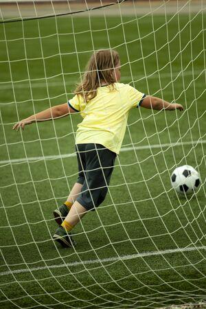 child run soccer (football) player. Boy with ball on green grass.