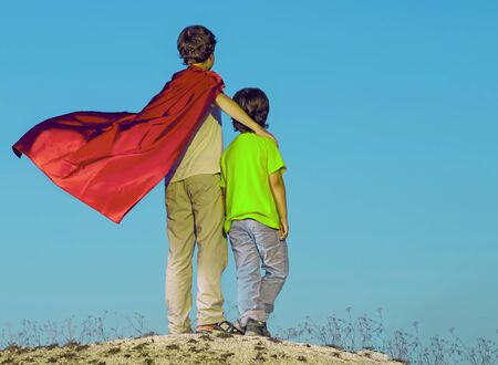 Two boys playing superheroes on the sky