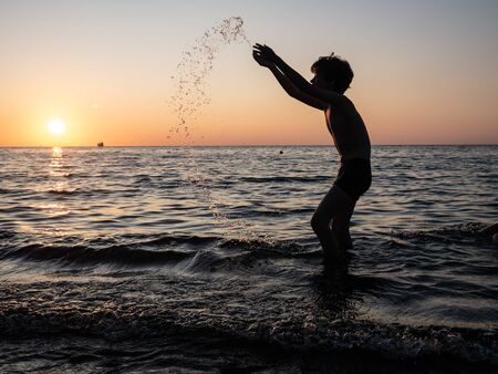 Boy splashing in sea with arms raised. Child play