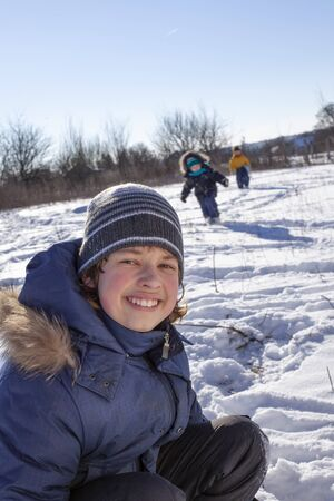 Winter children playing  outdoors during snowfall. Sunny day outoors leisure boys