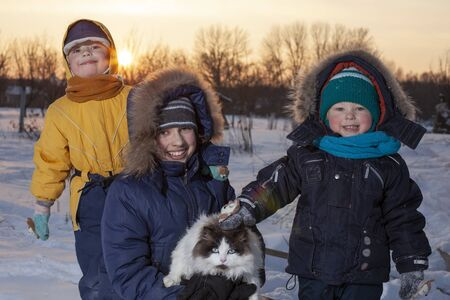 Winter children playing  outdoors during snowfall. Sunny day outoors leisure boys  with cat Stock Photo