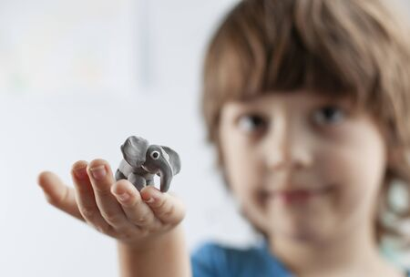 Cute little boy with elephant from plasticine on hand