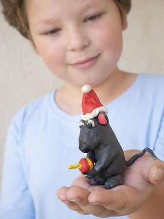 Cute little boy with rat mouse from plasticine on hand, christmas decoration, xmas toy,