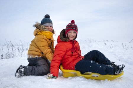 Two happy boys on sled in winter outdoors Standard-Bild