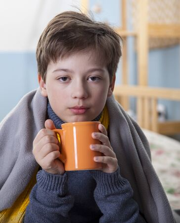 Sick boy with a cup of tea at home, flu virus Stock Photo