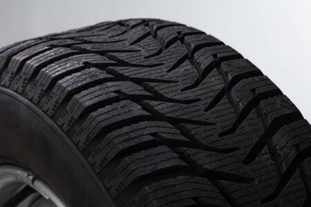 Winter studded car tire on grey background