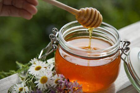 Miel en tarro de cristal y flores sobre un piso de madera.