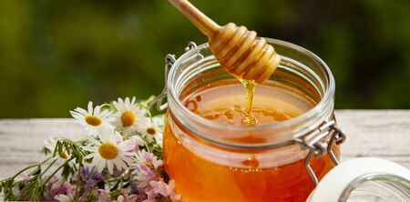 Honey in glass jar and flowers on a wooden floor.