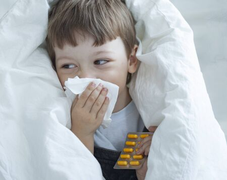 Little Boy blow her nose and get cold at home. Standard-Bild