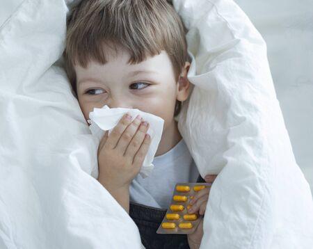 Little Boy putzt sich die Nase und wird zu Hause kalt. Standard-Bild