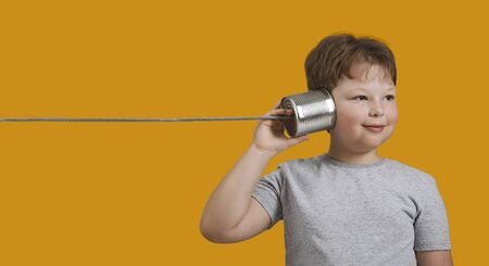 Boy Playing with Tin Can Phone. Isolated on Orange Background