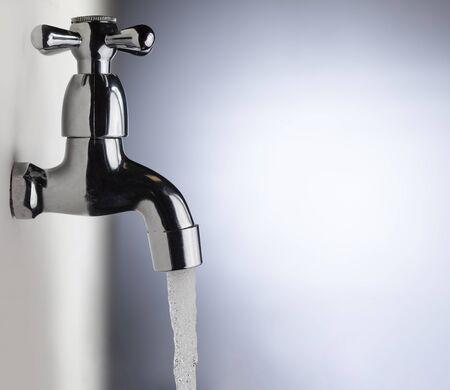 Wasser aus dem Metallhahn ablassen, Wasser fließt aus einem modernen Wasserhahn
