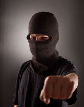 angry man in a balaclava on a dark background. Rebellious protester in a mask shows his fist.