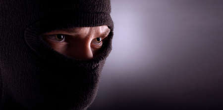 angry man in a balaclava on a dark background. Rebellious protester in a mask