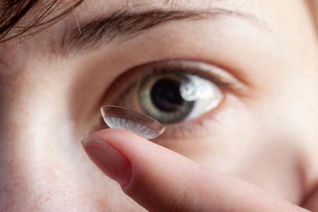 Girl with a contact lens on her finger (focus on the lens).