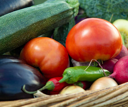 Different Organic Fruits and vegetables in basket on wooden table back.