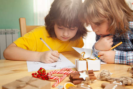 two Boys write a letter to Santa Claus. Near christmas tree. Merry Christmas and Happy Holidays.