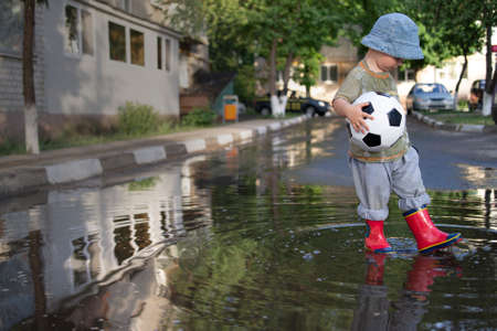 happy boy play in puddle with ball outdoors