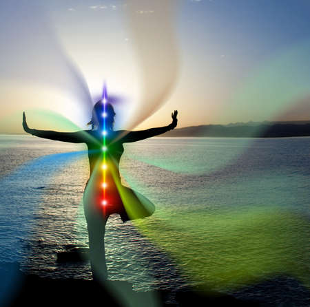 Woman in yoga pose on beach sunset view, glowing seven all chakra.