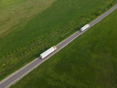 Two Truck with Cargo Semi Trailer Moving on Rural Road in Direction.