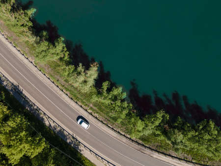 Aerial view of road between green summer forest and lake Standard-Bild