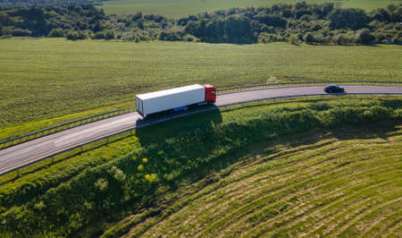 Truck with Cargo Semi Trailer Moving on Rural Road in Direction. Aerial top view
