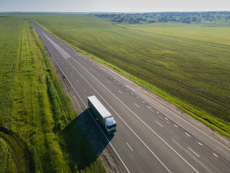 WhiteTruck with Cargo Semi Trailer Moving on Rural Road in Direction. Aerial top view Standard-Bild