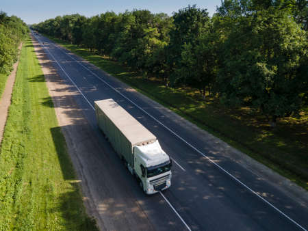White Truck with Cargo Semi Trailer Moving on Summer Road. Aerial top view Standard-Bild