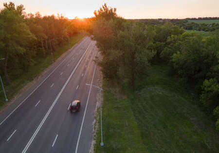 Car on road in the forest in summer time nature from air. View from a drone. Aerial view.
