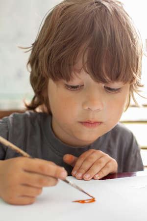 Children draw a picture in home, Boy studying paint with watercolors at school Standard-Bild