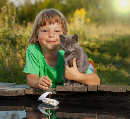 child and his friend kitten playing with a boat from water, pier in a river summer evening