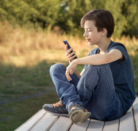 Teenager with Smartphone in Hand. Boy look in cell phone on summer background Standard-Bild